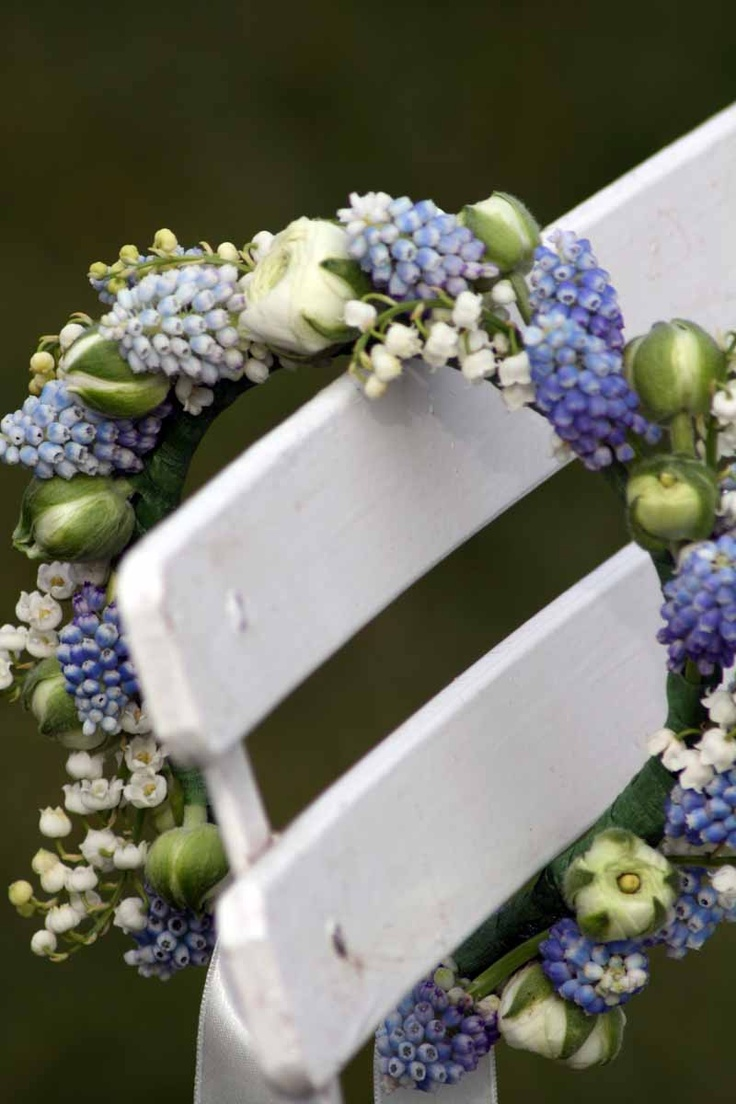 Flower crown of blue muscari, white ranunculus and lily of the valley