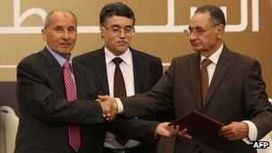 Libya's NTC hands power to newly elected assembly.NTC chief Mustafa Abdul Jalil (left)  the reins to the assembly's oldest member Mohammed Ali Salim