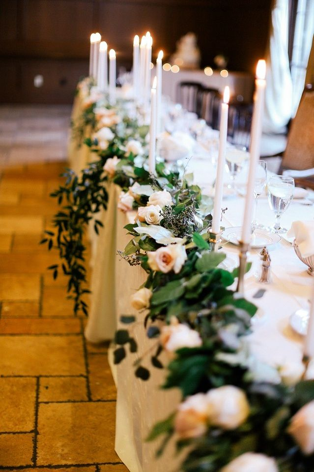 Long head table with blush roses and green leaves, hydrangea, and ivy draped over the front lined with long white tall candles | Feather& Twine Photography | villasiena.cc