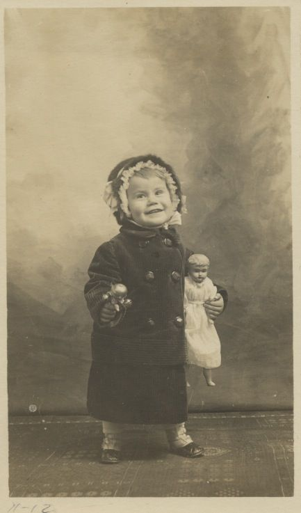 """Don't you just love this vintage photograph of a young child who is just absolutely beaming.Can anyone identify the doll she is holding?"" http://Theriaults.com"