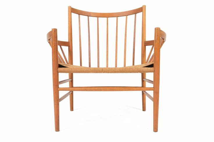 This stunning oak and paper cord lounge chair was designed by Jørgen Bækmark for FDB Møbler in 1963. This Model J82 features its original paper cord seat which is woven around a gorgeous oak frame. The high back gently bows for a comfortable seating experience. In excellent original condition with typical wear for its vintage.