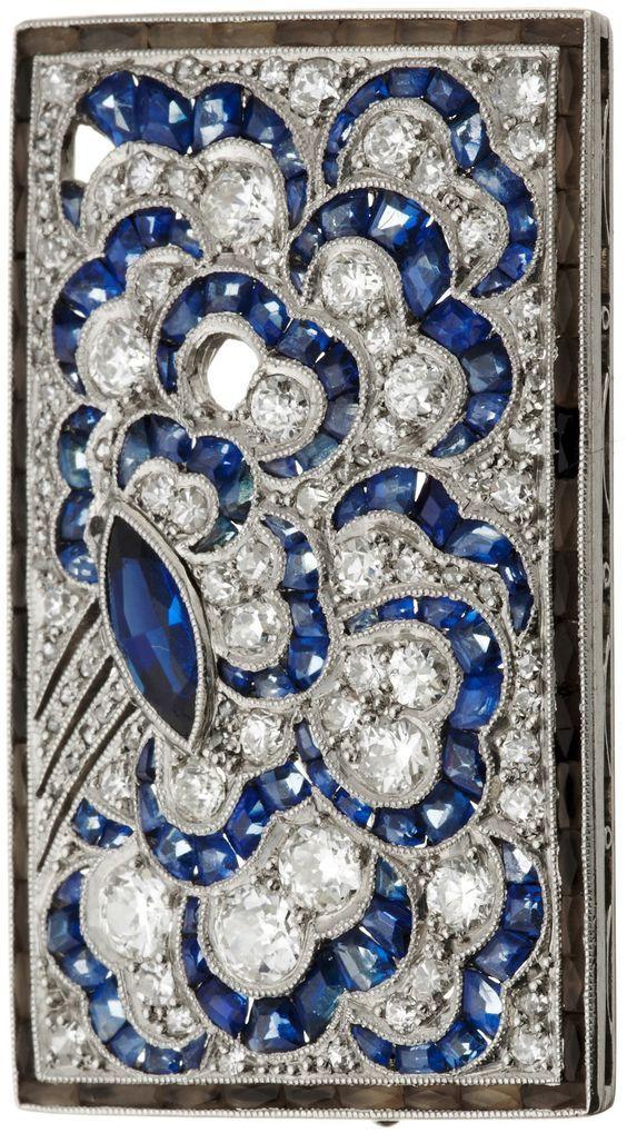 An Art Deco platinum, diamond and sapphire brooch, circa 1920. 3.5 x 2.5cm.
