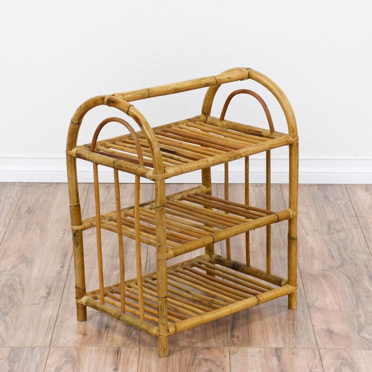 This small tropical shelf is featured in a rattan with a glossy bamboo finish. This end table magazine rack is in great condition with 3 tier shelves, curved bent details and a top handle. Beach chic bookcase perfect for organizing books and magazines! #tropical #storage #bookcase&shelving #sandiegovintage #vintagefurniture