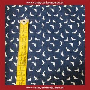 Tela con motivo de delfines sobre fondo azul marino, doble ancho, corte desde 25cms. Corte desde 25cms x 145cms
