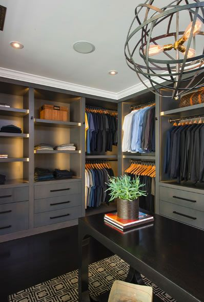 Grand bedroom turned walk-in closet system with wall to tall gray cabinetry with black hardware and gray shelves with lighting from both pot lights and a contemporary orb chandelier. Centering the room below the chandelier is a black lacquered console table sitting atop a black and cream geometric rug.