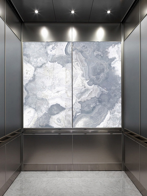 LightPlane Panel with ViviStone Pearl Onyx glass, Pearlex finish shown illuminated in a LEVELe-106 Elevator Interior with large accent panels in ViviChrome Chromis glass with Slate Blue interlayer and Pearlex finish; small accent panels in Stainless Steel, Seastone finish; Quadrant handrail