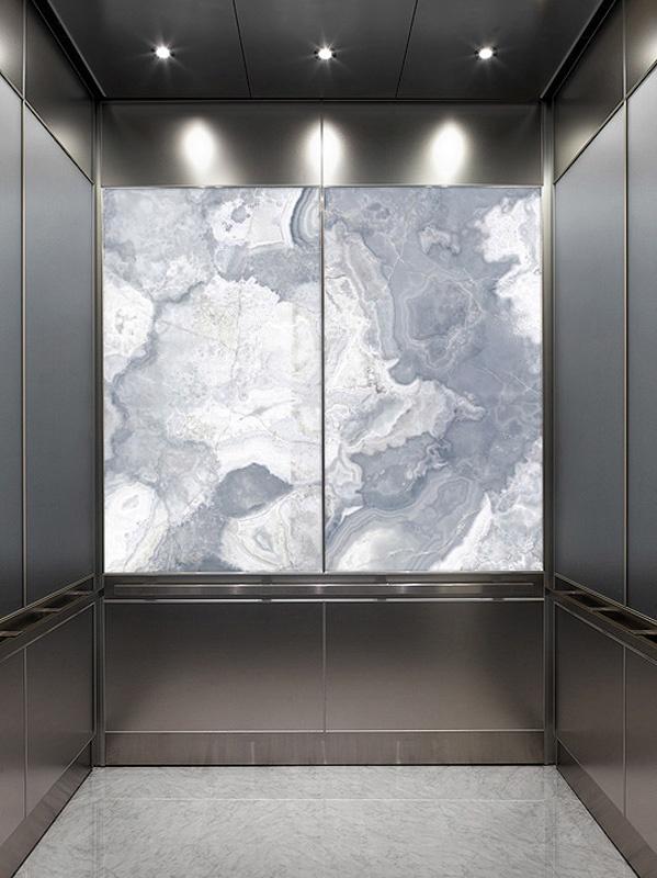 LightPlane Panel with ViviStone Pearl Onyx glass, Pearlex finish shown illuminated in a LEVELe-106 Elevator Interior with large accent panels in ViviChrome Chromis glass with Slate Blue interlayer and Pearlex finish; small accent panels in Stainless Steel, Seastone finish; Quadrant handrail