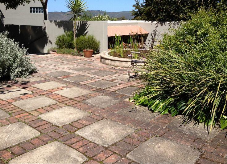 Eenvoudige bestrating, diverse planten en grijze muren