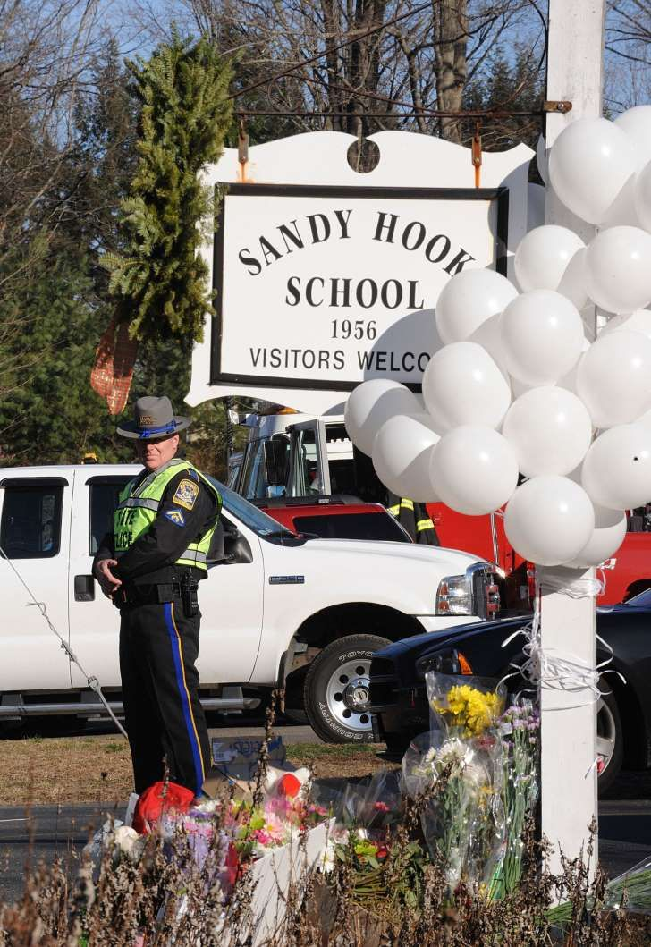 Police officers stand at the entrance to the street leading up to Sandy Hook Elementary School on Saturday, December 15, 2012, in Newtown, Connecticut, a day after a shooting where 26 people died. (Olivier Douliery/Abaca Press/TNS)
