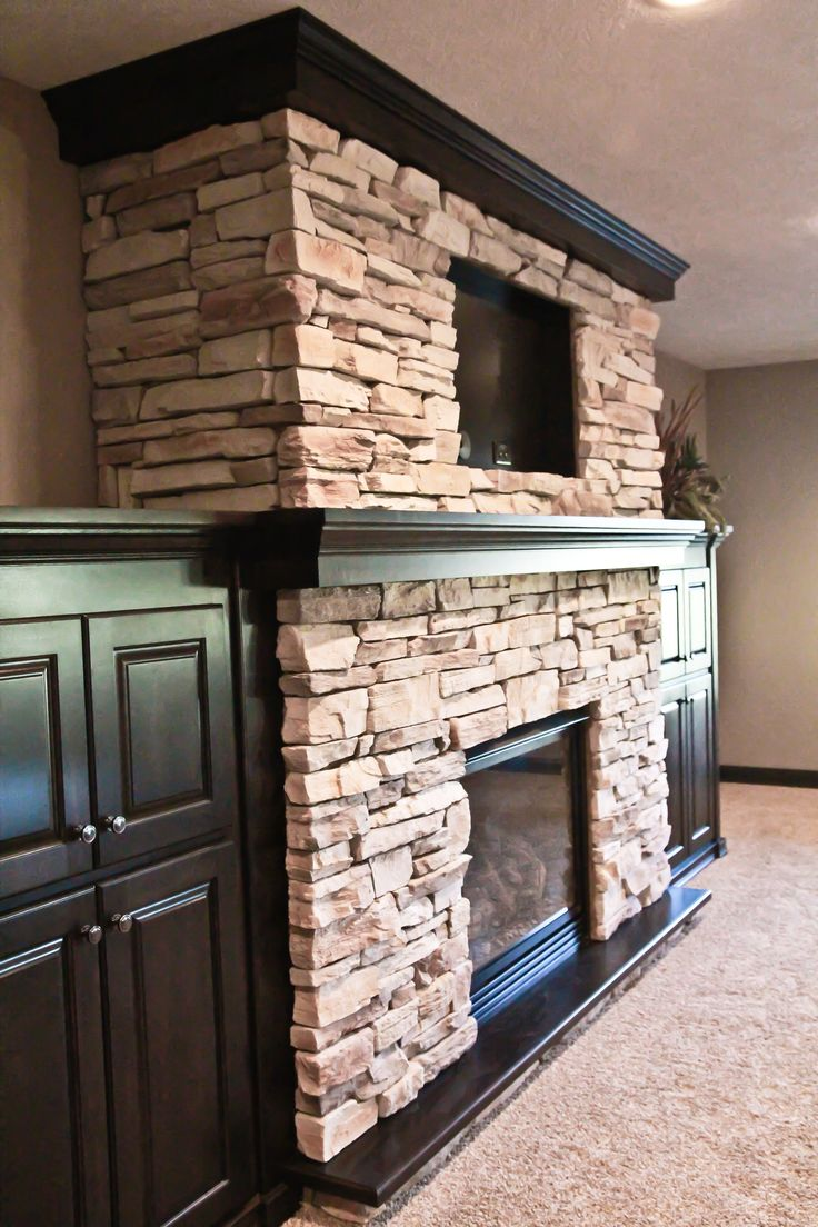 wood mantle; stone fireplace, built-ins around fireplace, TV above fireplace