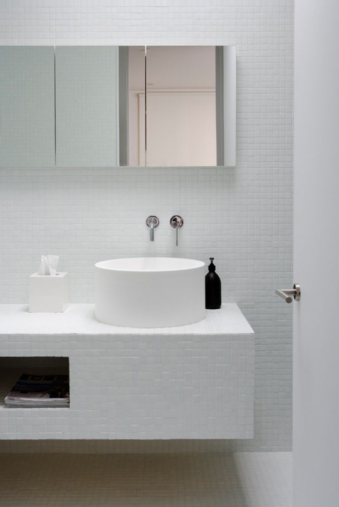 white bathroom with round basin and mirrored cabinets