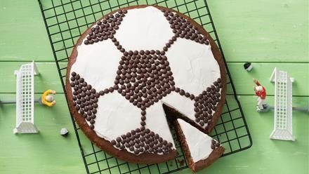 Fußballkuchen   Hier rollt der Fußball über den Kuchentisch: Backrezept für einen schokoladigen Fußballkuchen - der gelingt einfach mit der Springform und ein wenig Geduld. Ein Rezept von und mit Sanella.