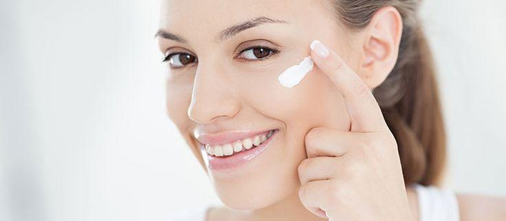 Usmiata žena si aplikuje na tvár očný krém