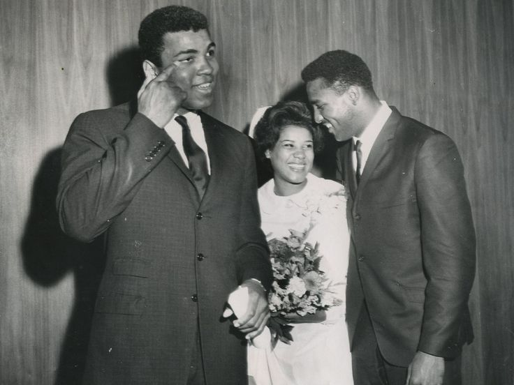 Muhammad Ali brushes a tear from his eye as he congratulates his sister-in-law Sandra Pickett Ali, on her graduation from nursing school in Chicago Oct. 3, 1966. Her husband, Ali's brother, Rahaman, smiles happily at the commencement exercises.  UPI