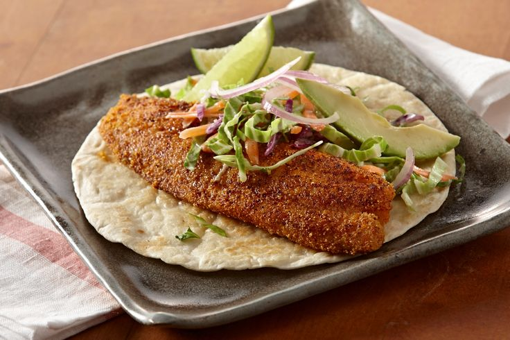 These simple fish tacos feature spiced tilapia and cilantro coleslaw. Sliced avocado and lime wedges make great accompaniments to the chili powder kick!