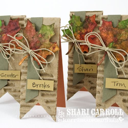 Cute & simple place cards - cut corrugated cardboard and colored card stock together & glue, bend in half & glue a strip of ribbon, a silk leaf, a bit of twine & write guests name on colored card stock!