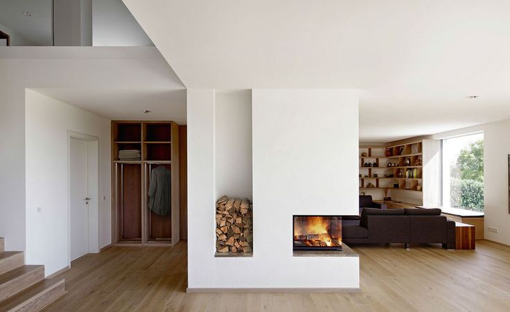 Cut-away corner fireplace looks like it's floating, set-off nicely by the rebated log pile