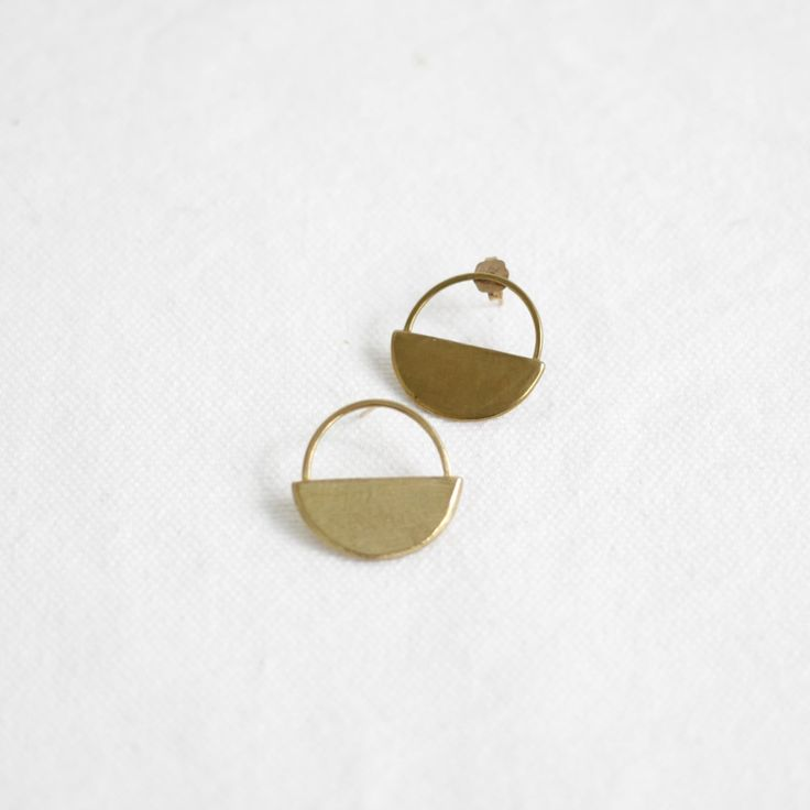"""Meet your new favorite, throw-on-with-anything earrings. They look amazing  with pretty much anything; wear with your favorite date night dress or  elevate a casual look of jeans and a tee.  Brass circle with half circle shaped hand soldered earrings on 12k gold  posts and back.      * Made locally in Portland, OR by Seaworthy.     * circles are just under 1"""" in length and width  ABOUT THE MAKER  """"Designer and self-taught jeweler, Marisa Howard, finds inspiration in a  variety of…"""