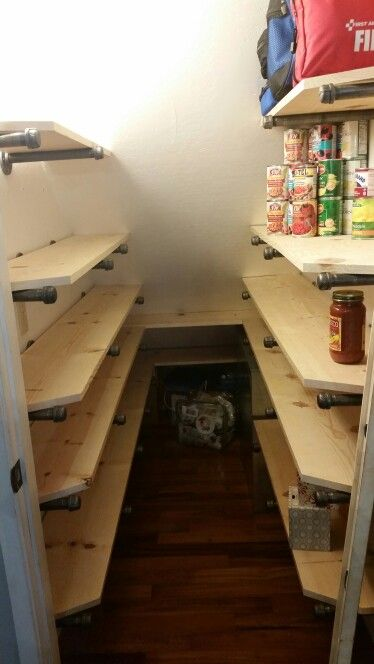 """Industrial pantry shelving under the stairs. 3/4"""" Galvanized pipe, flanges and caps. Turned our closet into TONS of useful storage. 12"""" deep on right (4 cans deep, 3 high) around AC return, 10"""" deep on left. Tons of storage. There are 4 flats of large water bottles stacked in the very back completely out of site for emergencies."""