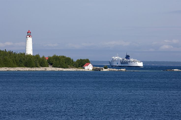 The M.S. Chi-Cheemaun passes by Cove Island Lighthouse. Tobermory, ON
