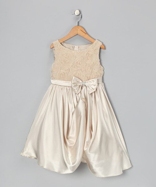 Folds of glossy, flowing fabric give this fancy frock an extra heap of sweetness, while its back tie and zipper fasten faster than a fairy can flap her wings. Plus, swirls of rosettes create an enchanting flower garden across its bodice that's plotted perfectly atop the silky-soft skirt.100% polyesterHand wash; hang dry