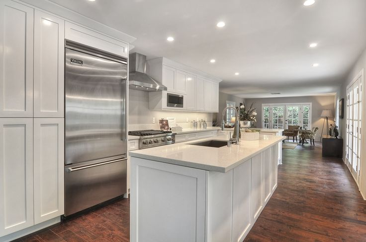 The kitchen features custom cabinets, Silestone countertops, recessed lighting, island, breakfast bar and nook. The stainless steel appliances include Viking refrigerator, range and dishwasher, GE microwave, and Avanti wine cooler and beverage center. | 1261 Triumphal, North Tustin