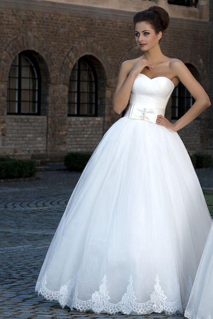 Krásne svadobné šaty so širokou sukňou zdobenou čipkou bez ramienok zdobené mašľou