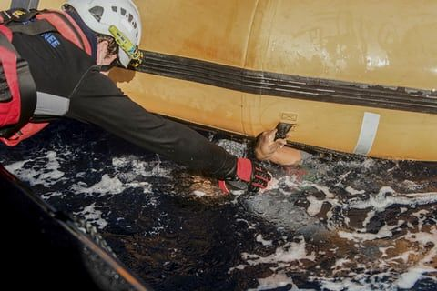 A rescuer reaches for the hand of a man from under a dinghy boat as some 800 migrants and two bodies were recovered from the Mediterranean.