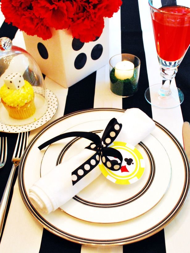 Carry the bold, colorful theme through to the place setting. Kelly placed a crisp white napkin, tied with a whimsical polka-dot ribbon and a poker-chip tag by WH Hostess, atop standard white plates. Fill votive candles with green sprinkles to portray the traditional green color on game tables, and serve red champagne punch for an extra pop of color.