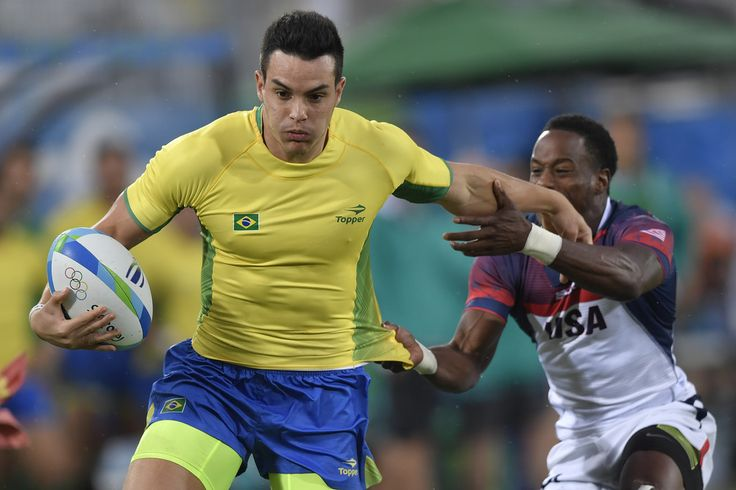 Brazil's Daniel Sancery (L) hands off USA's Carlin Isles in the mens rugby sevens match between USA and Brazil during the Rio 2016 Olympic Games at Deodoro Stadium in Rio de Janeiro on August 10, 2016. / AFP / PHILIPPE LOPEZ