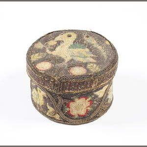 A 17th century needlework trinket box  Of circular form, with a removable lid inscribed around the rim with 'Sith [Since] all is vanity, waste for eternity', embroidered with birds, insects and flowers in silk tent stitch, with applied scrolling metal braid, the box of wood, lined with silk,  4 x 7cm.