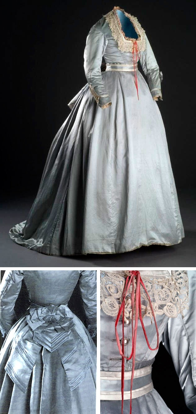 Silk satin dress, ca. 1865-70, in gray-blue. Boned bodice has square neckline trimmed with ivory silk satin ribbon, red silk velvet ribbon, and Valenciennes lace. Same trimming is repeated on sleeves. Closes in front with 4 pearl buttons. Bodice lined in cotton. Skirt shows transition from full crinolines to flat fronts and bustles. Museo del Traje