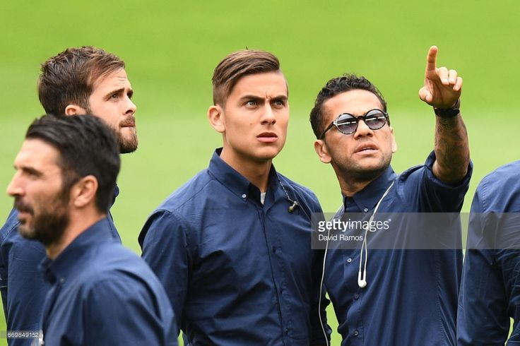 Paulo Dybala and Dani Alves of Juventus walk on the pitch prior to the Juventus press conference at the Camp Nou on April 18, 2017 in Barcelona, Spain.