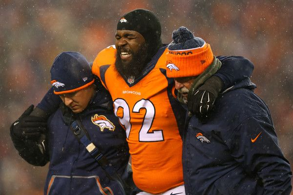 Nose tackle Sylvester Williams #92 of the Denver Broncos is helped off of the field after an injury against the New England Patriots at Sports Authority Field at Mile High on November 29, 2015 in Denver, Colorado.