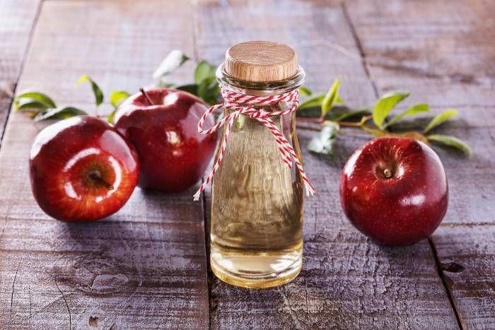 Vinagre de manzana sobre fondo de madera rústica