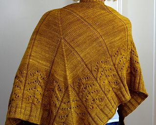 """""""Comfort and joy"""" is a triangle shaped shawl, knit from the top down with an easy lace pattern combined with cables."""