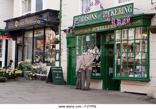 Mature couple are window shopping at a jewellers in Market Place, Pickering, an attractive town in North Yorkshire, England, UK. - Stock Image