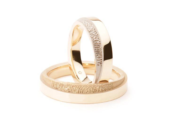 Bij deze geelgouden trouwringen lijkt het optisch alsof de ring uit een onder- en een bovenring bestaat. De ring is echter uit één stuk gegoten. De onderring steekt uit ten opzichte van de bovenring. Hierop is de vingerafdruk geplaatst. Bij de damesring is deze wit verguld.