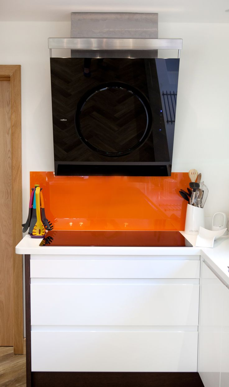 Beautiful Metris Curved Kitchen in Porcelain and Wenge with bright orange glass splash backs for a pop of colour.