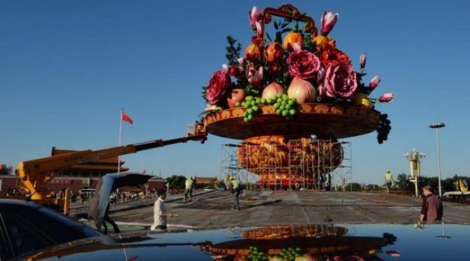 Pot raksasa berwarna merah itu memiliki tinggi 13 meter dan berdiameter 11 meter. Isinya: Bunga mawar imitasi, buah persik dan anggur.