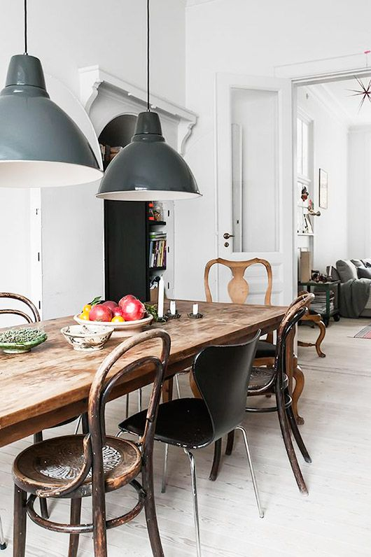 mismatched chairs around a rustic modern table with industrial pendant lights via kinfolk / sfgirlbybay