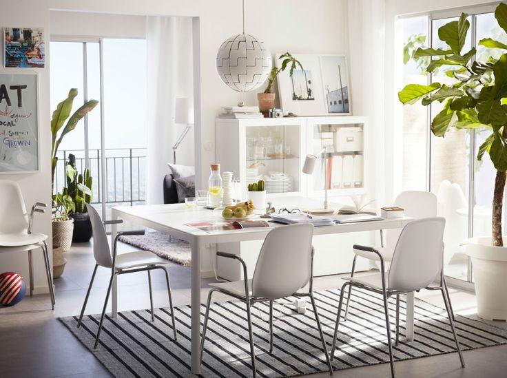 Ein helles Esszimmer, u. a. eingerichtet mit einem großen weißen Tisch und vier LEIFARNE Armlehnstühlen weiß/verchromt