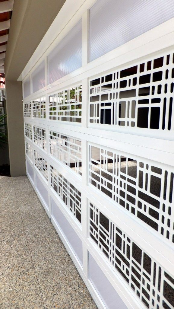 Custom laser-cut panels with matching fencing. You-Design-It Custom Made Garage Doors.