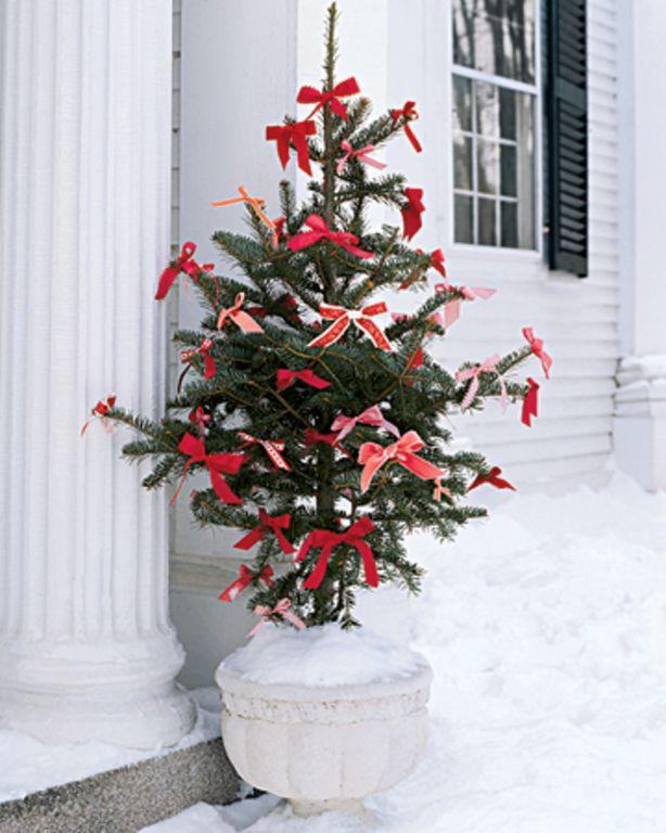 kerstboom met rode strikken als versiering.