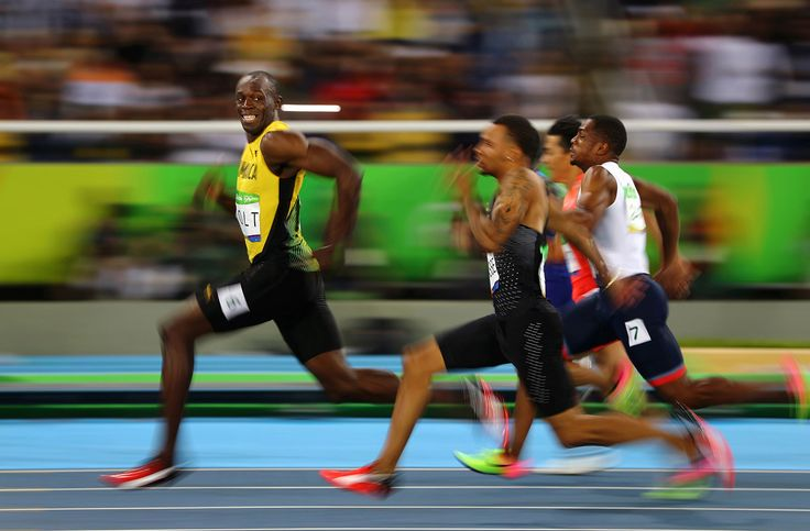 Sports, Third Prize, Singles—<i>Rio's Golden Smile</i>: Usain Bolt of Jamaica smiles as he looks back at his competition, while winning the 100-meter semi-final sprint, at the 2016 Olympics in Rio de Janeiro, Brazil. Bolt is regarded as the fastest human ever timed. He is the first person to hold both the 100-meter and 200-meter world records since fully automatic time became mandatory.