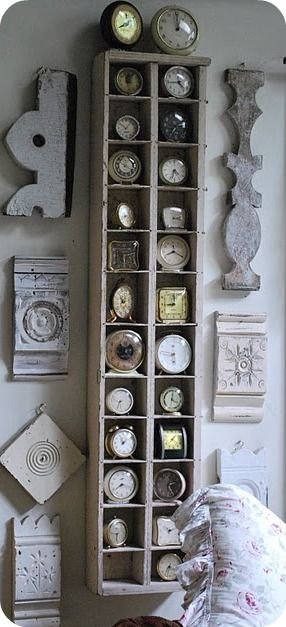 A collection of vintage clocks is displayed in an antique shelving unit flanked by architectural salvage pieces: