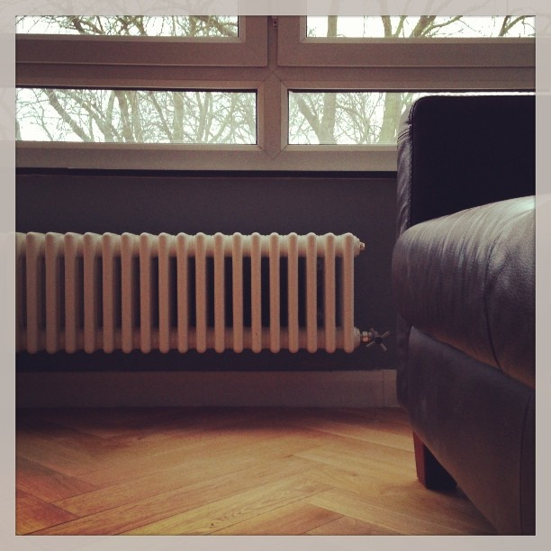 Old fashioned radiator with parquet floor.