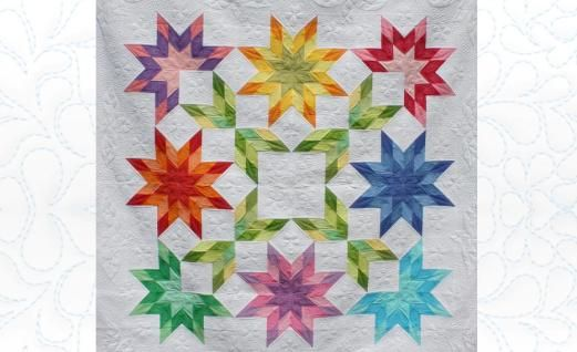 """Jelly Roll Strip Starburst Quilt-BY: Kimberly Einmo.. Kimberly designed this cheerful quilt to be made using just one Jelly Roll fabric bundle (or 40 – 2½"""" strips) plus one background fabric. After the top was constructed, Birgit took the quilt top, Fairfield's wool batting, and backing fabric back to Germany in her luggage where she added the exquisite machine quilting using motifs inspired from the Plumeria blossoms blooming in Kimberly's back yard."""