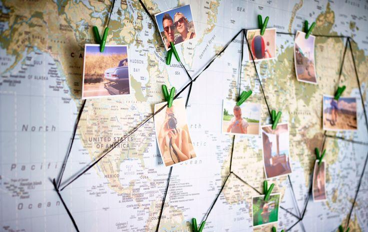 Nahaufnahme einer Landkarte mit Fotos, die in einem Netz von Fäden und Wäscheklammern miteinander zu einer Reise-Collage verbunden wurden, u. a. mit TORKIS Korb mit 30 Wäscheklammern in Weiß/Grün und FRAMSTÄLLA Band in Schwarz