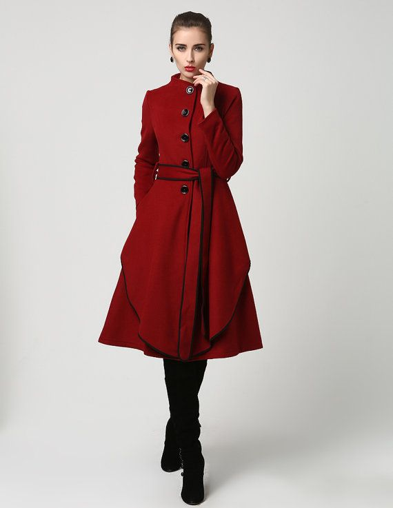 So stunning, this 70% cashmere coat features a collar less style and oversized button closure with long self tie belt that has been trimmed in black.